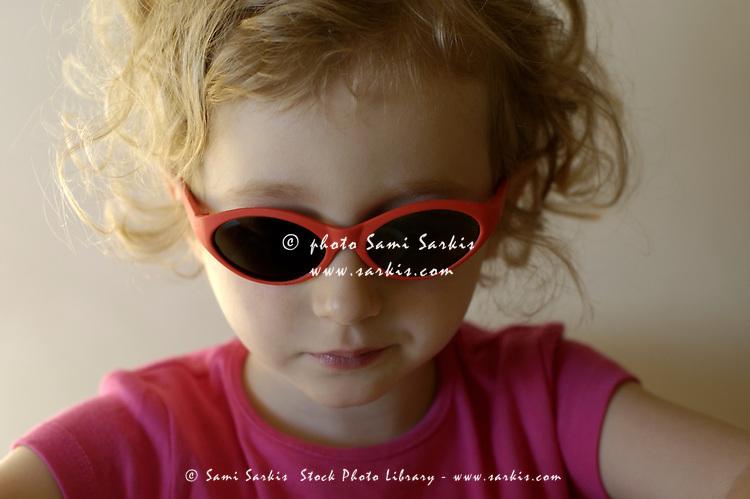 Little blond girl wearing sunglasses.