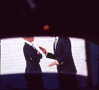 Man & Woman executives in suits arguing, seen through limousine window