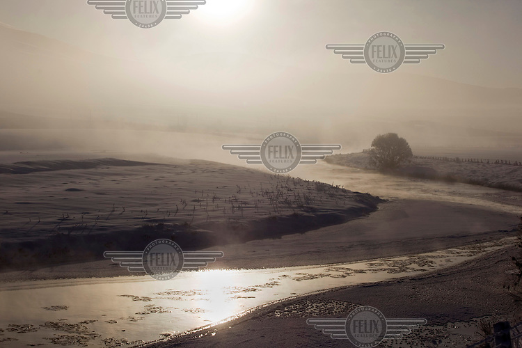 Mist rises over the river Clyde where it flows close to its source near Biggar, South Lanarkshire. Temperatures plunged to - 14C on this particularly cold January day causing the river to partially freeze.