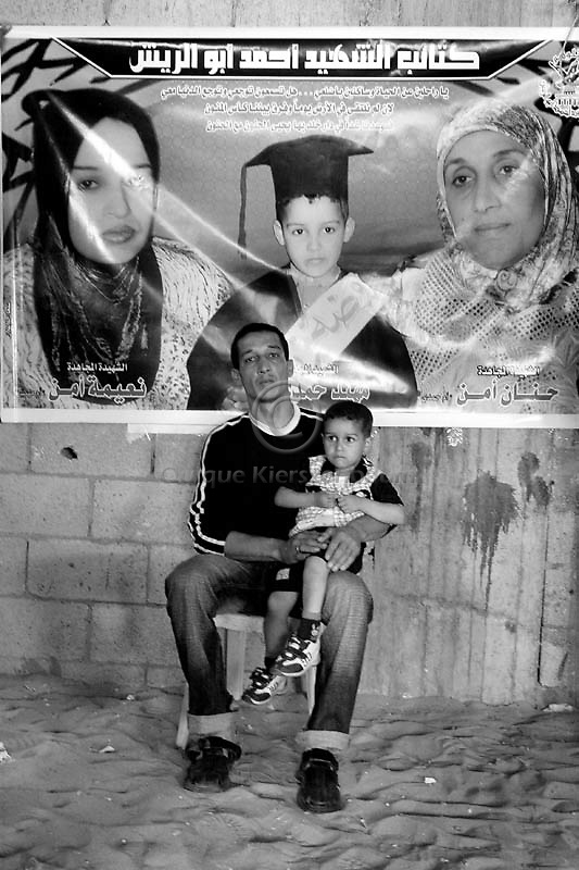 With a poster announcing the death of his wife, Naima, his mother Hanan and his son Muhaned in the background Hamdi Aman, 28, holds his son Mumin, 2 in their home in Gaza City, May 28, 2006. Hamdi and Mumin survived an Israeli air strike as Israel Air Force targeted the Islamic Hamas leader Mohammed Dadouh, when the family was in a car next to the jeep of the Islamic Jiahad leader Saturday, May 20, 2006. As a result of the strike Hamdi's wife, Naima, his mother Hanan and his son Muhaned were killed. A seven-year-old daughter Mariya was seriously injured in the attack also. Photo by Quique Kierszenbaum..