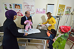 Dr. Husein Mady prepares to pass a Syrian refugee child to nurse Fadia El Malt in a clinic in the town of Kamd El Loz, in Lebanon's Bekaa Valley. Run by the Amel Association, the clinic's work with refugees is supported by International Orthodox Christian Charities, a member of the ACT Alliance. The girl's mother and siblings observe..