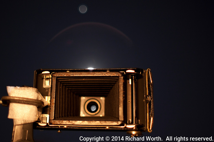 From the backside of a Jiffy SIX-20, the January Full Moon appears; through the antique camera's lens, in a refractive image in the sky above, and a bright tiny sliver on the camera's edge.