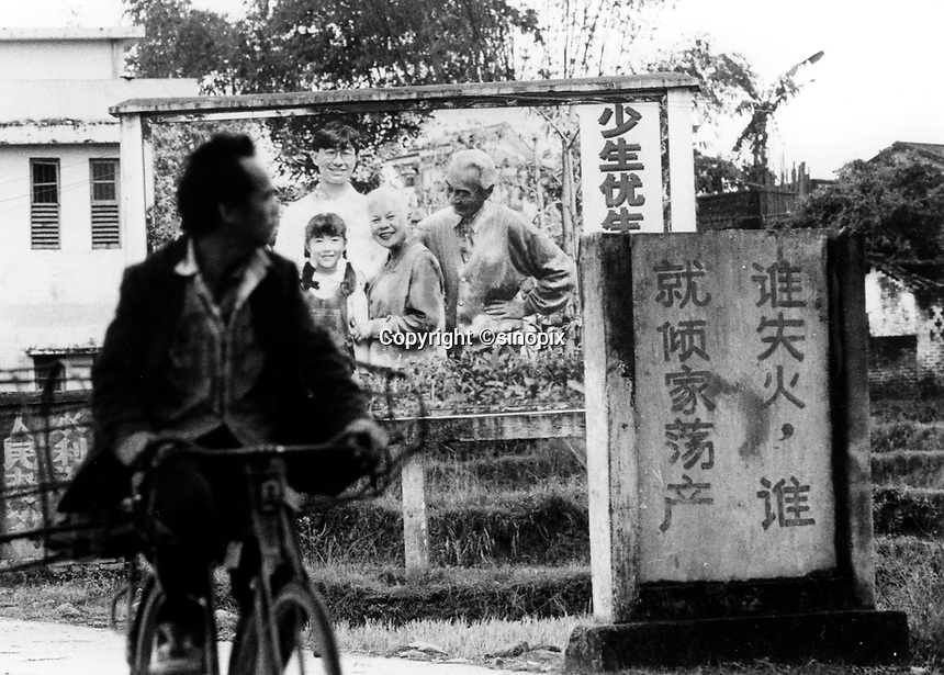 A cyclist passes a propaganda poster that lets villagers know the  benifits of the One Child Policy&quot; in Huaji County. The One Child Policy has been used as a stick to extort fines from the farmers. The poverty gap in China is a major theme at this years National Perople's Congress in Beijing since it is causing destabilisation of the country as farmers sick of corrupt official take matters into their own hands.<br /> 25 Mar 2005<br /> <br /> photo by Richard Jones / Sinopix