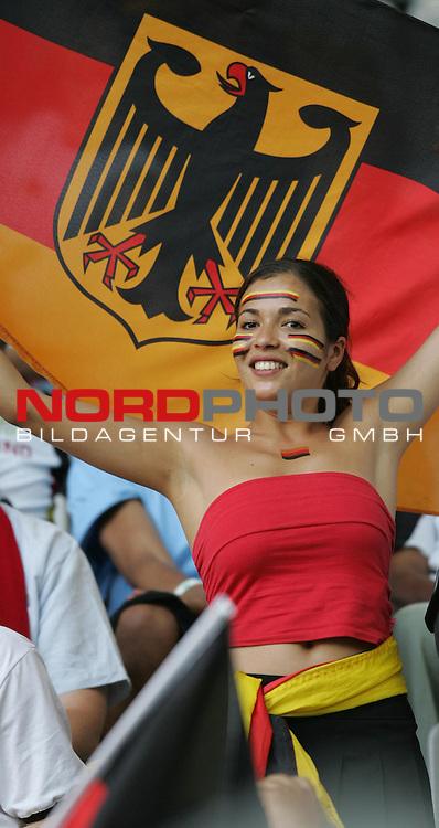 FIFA WM 2006 -  Semi Finals / Halbfinale<br /> Play    #61 (04-Juli) - Deutschland - Italien<br /> <br /> Attaktiver weiblicher Deutscher Fan mit Deutschlandfahne im Hintergrund.<br /> <br /> Foto &copy; nordphoto