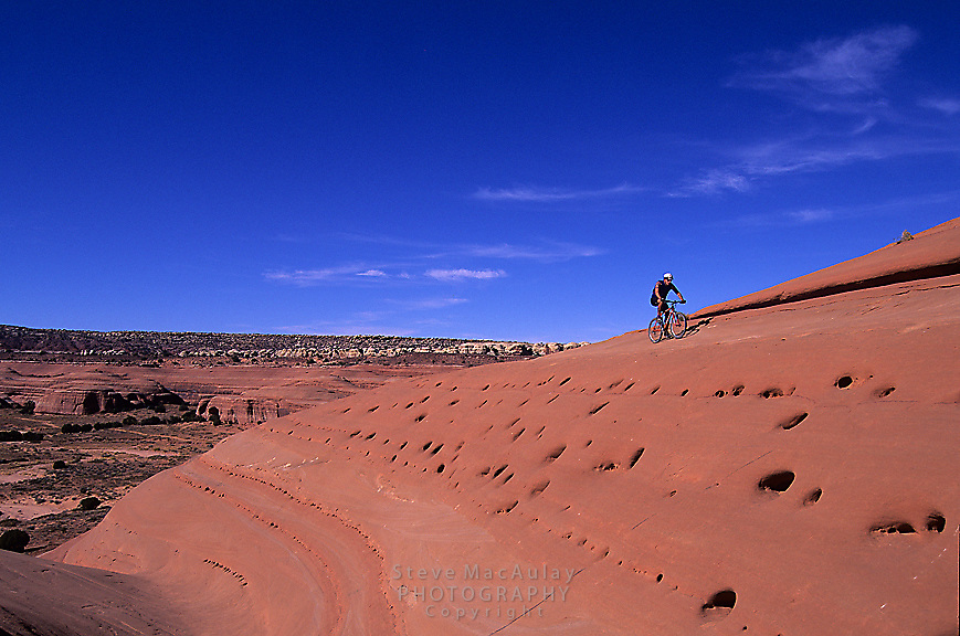Mountain biker crosses wildly pocketed sandstone slope, Bartlett Wash, Moab, Utah.