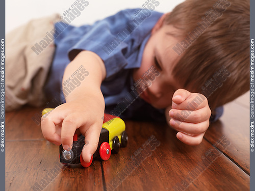 Boy playing with a toy train lying on hardwood floor