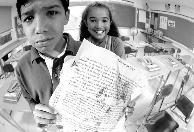 worried schoolboy hands in very messy paper