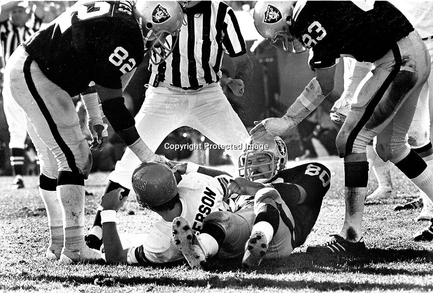 Oakland Raiders Art Thoms, Horace Jones and Ted Hendricks over sacked quarterback Cincinnati Bengal Ken Anderson. (1975 photo/Ron Riesterer)