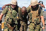 Plainfield, NJ native LCpl. Rande Johnson (Communications Platoon, H&S Co. 1st Battalion, 4th Marines) is helped inside after succumbing to heat and extertion while taking part in early morning excercise or Physical Training (PT). Aboard ship, Marines are required to take part in PT six days a week, often while carrying their weapons and fully dressed in boots and body armor, to prepare themselves for the rigors of the upcoming deployment in Iraq.