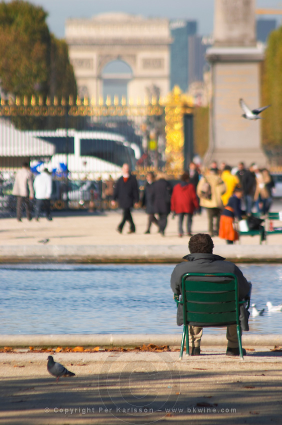 In the Jardin des Tuileries garden park, a man sitting in a green metal chair by a fountain, Arc de Triomphe in background. Paris, France.