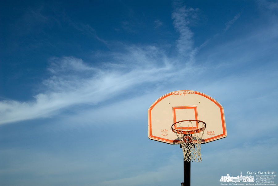 A basketball backboard and net against a blue sky.<br />