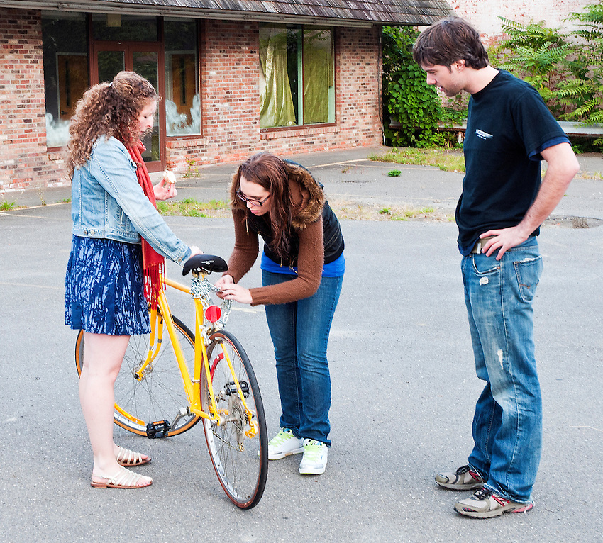 Rachel Bird and Kaitlyn McInnes work on the bicycle while Brian McAllister looks on.