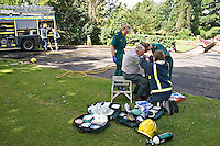 Ambulance paramedics and firefighters attending patient with burns