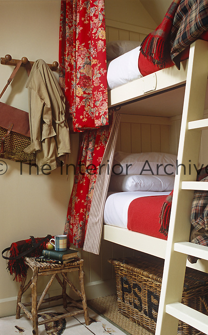 The wooden bunk beds have matching red blankets and red floral curtains lined with ticking