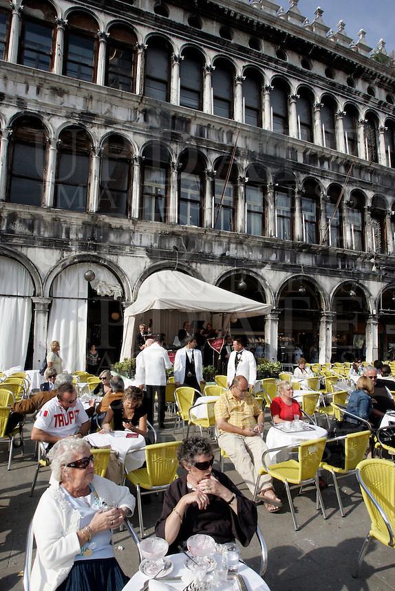 Turisti seduti nei bar all'aperto ascoltano la musica suonata dalle orchestre, in Piazza San Marco a Venezia.<br /> Tourist sit at outdoor cafes as orchestras play in St. Mark's Square, Venice.<br /> UPDATE IMAGES PRESS/Riccardo De Luca