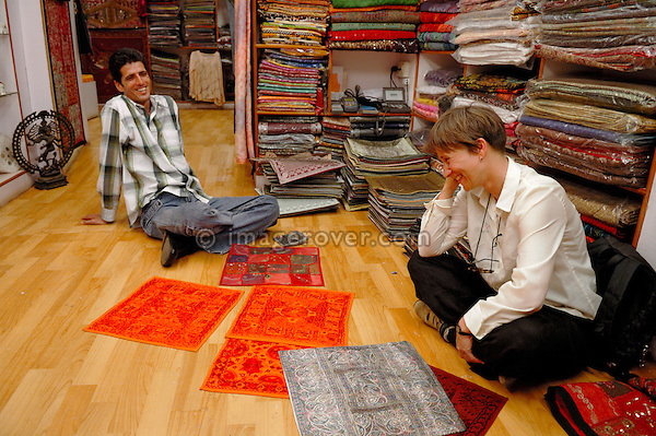 German female tourist negotiating prices for typical indian fabrics in a small boutique in the jewish part of Cochin (Kochi). Cochin, Kerala, India.