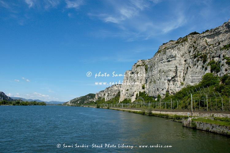 Railway along the Rhone River and massive limestone cliffs, Drome, France.