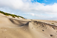 Footprints cover dunes in dramatic seascape of Pacific Ocean beach at Nehalem Bay State Park, Oregon State Parks.  Astoria, Oregon Use of this image licensed exclusively by Spaces Images, www.spacesimages.com.
