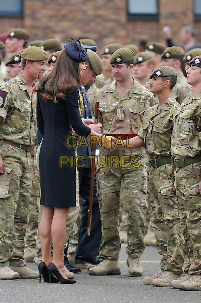 Catherine, Duchess of Cambridge Prince William, Duke of Cambridge and Catherine, Duchess of Cambridge present Afghanistan campaign medals to the 1st Battalion Irish Guards, Victoria Barracks, Windsor, Berkshire .England, UK, 25th June 2011..full length coat uniform military side   Kate Middleton princess black hat  gold brass buttons  royal shoes  soldiers army  back rear behind shaking hands .CAP/CAS.©Bob Cass/Capital Pictures.