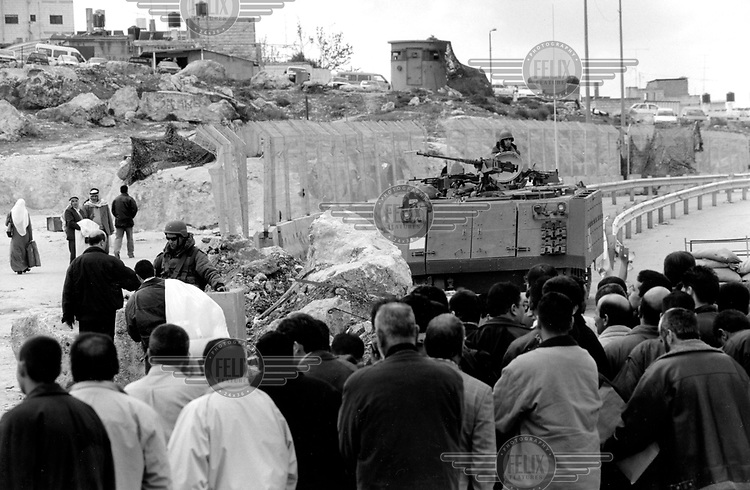 ©JC Tordai/Panos Pictures..West Bank, Palestine. Israel. April 2002..Palestinians line up to cross a checkpoint Kalandia.