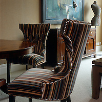 In a suite of the Soho Hotel in London the dining chairs around a circular table are upholstered in a stunning multi-coloured striped fabric