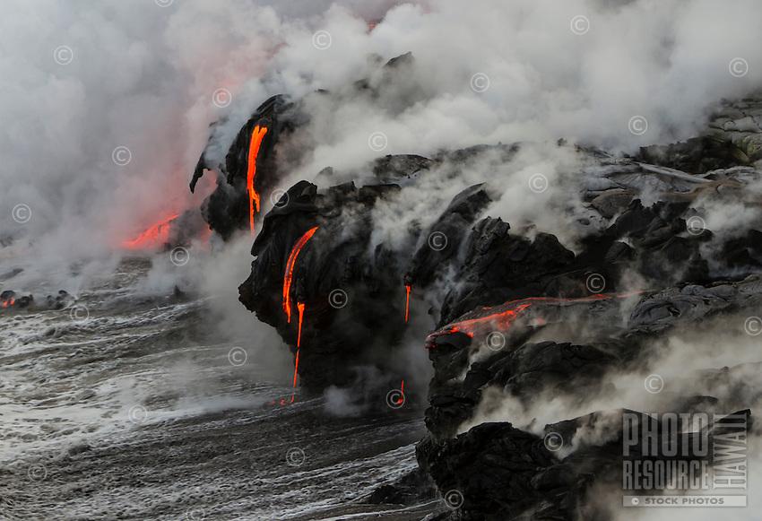 Glowing, flowing lava enters sea at Hawai'i Volcanoes National Park and the Kalapana border, Big Island.