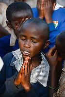 KENYA Thika near Nairobi, Primary schhol, Simbi Roses a fair trade rose flower farm has donated school furniture, toilets, water supply and class room renovations from fair trade premium, children at prayer / KENIA Thika bei Nairobi, Grundschule, Simbi Roses eine fairtrade zertifizierte Blumenfarm hat mir fairtrade Praemien neues Schulmobilar und Renovierung von Klassenraeumen unterstuetzt, Kinder bei einem Gebet