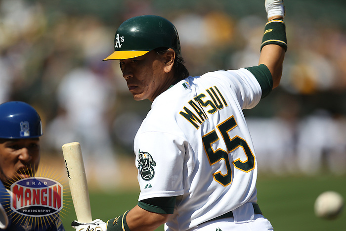 OAKLAND, CA - SEPTEMBER 5: Hideki Matsui #55 of the Oakland Athletics waves a base runner home as Kansas City Royals catcher Salvador Perez #13 chases a wild pitch during the game at O.co Coliseum on September 5, 2011 in Oakland, California. Photo by Brad Mangin