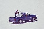 MEN ENJOY OFF ROADING IN TRUCK ON SAND DUNES