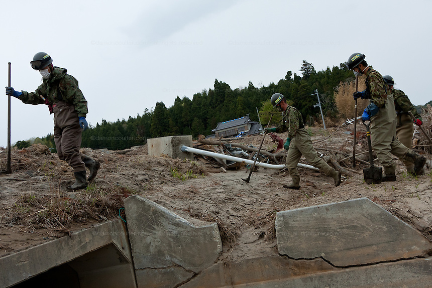 Soldiers from the Japanese Self Defense Force (JSDF) search for bodies and other items in the mud near Minami Soma, Fukushima, Japan Tuesday, May 3rd 2011. Minami Soma is on the edge of the 20 kilometre nuclear contamination exclusion zone around the Fukushima Daichi nuclear power station.