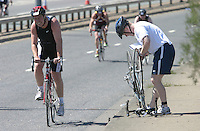 04 AUG 2007 - LONDON, UK - An age group competitor makes a roadside repair - London Triathlon. (PHOTO (C) NIGEL FARROW)