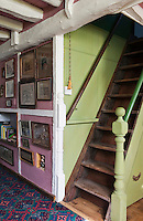 The walls adjacent to the ladder staircase have been painted a creamy pistachio green in contrast to the strawberry-pink walls of the living room
