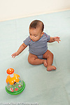 6 month old baby girl sitting viewing interesting toy