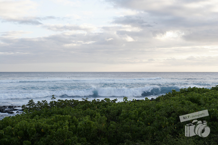 Surfing and body boarding in Hawaii, on the south shore of Kauai with some of the most beautiful shoreline scenery.