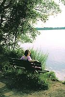 Woman age 35 thinking on bench at Lake Harriet.  Minneapolis Minnesota USA