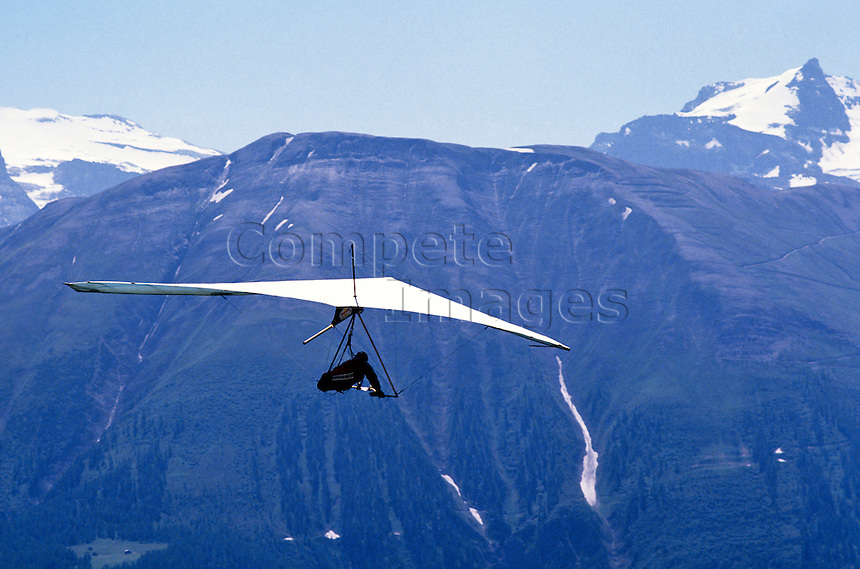 Hang gliding over snow capped mountains
