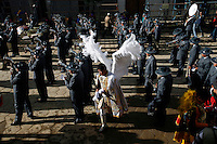 A man dressed in an angel costume walks through a band during a performance at the Carnaval de Oruro. During the fiesta many people sacrifice llamas and give offerings such as coca leaves and cigarettes to show their dedication to the Devil, a Virgin, Pachamama or Mother Earth. The Devil (or Uncle) is a mythical character that protects the miners of Oruro who work in dangerous conditions hundreds of metres below the ground. During the carnival, people dress in outrageous costumes and dance for days before arriving at the Church of Socavon, where they pay their respects to a virgin. Ironically, many of the dancers wear devil costumes.