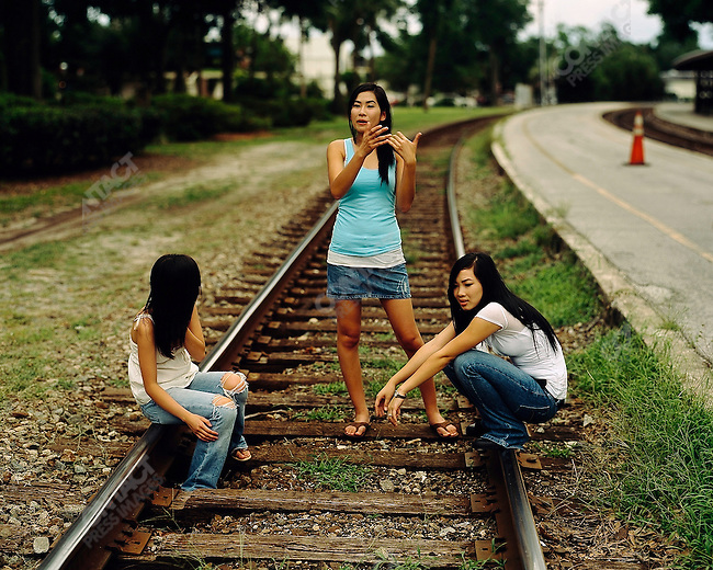 Vietnamese girls hanging out by the traintracks in Winterpark, a suburb of Orlando, after seeing a friend of on the train. Orlando, Florida.  June-October 2006.