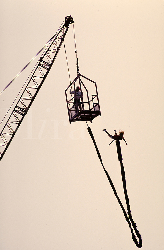 Bungee jumper leaping from a crane, adrenaline, risk; NR.