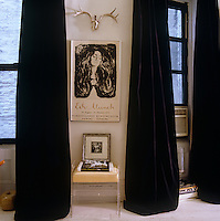A vintage poster from an Edward Munch exhibition in the 1970s hangs between a pair of long black velvet curtains