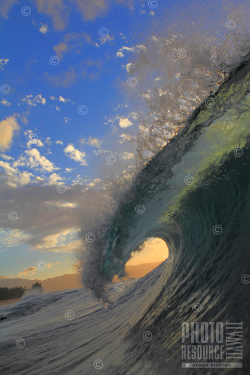 Beautiful sunset sky behind a breaking wave at Rockpiles on the North Shore of Oahu