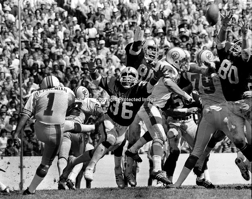 Oakland Raiders beat Miami Dolphins Sept 23,1973 at U.C.Berkeley to end the Dolphins NFL win streak of 18....Kicker Garo Yepremian, Raiders Bob Hudson and Art Thoms try to block, . (1973 photo/Ron Riesterer)