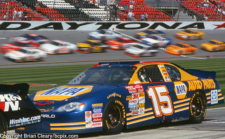 The #15 Chevrolet Monte Carlo of Miachael Waltrip sits on pit road as a pack of cars races past during practice for the Daytona 500, Daytona International Speedway, Daytona Beach, FL, February 2001.  (Photo by Brian Cleary/www.bcpix.com)
