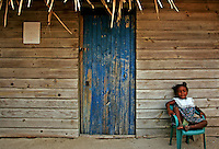 A little girl sits in front of her house in Chachauata Cay, Honduras August 8, 2007..Born in Argentina, photographer Ivan Pisarenko in 2005  decided to ride his motorcycle across the American continent. While traveling Ivan is gathering an exceptional photographic document on the more diverse corners of the region. Archivolatino will publish several stories by this talented young photographer..Closer look at  Ivan's page www.americaendosruedas.com...