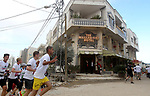 Participants run past the the Walled-Off Hotel, Banksy's newly opened hotel, next to Israel's controversial separation wall, during the fifth Palestine Marathon in the biblical West Bank town of Bethlehem, on March 31, 2017. Photo by Wisam Hashlamoun