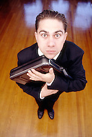 Stock Photo looking down on a young business man with eyes wide who is holding his briefcase tightly.