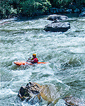 A man rides a kayak on the Gallatin River in Montana. People kayak on the Gallatin Rvier, between Big Sky and Bozeman, Montana.