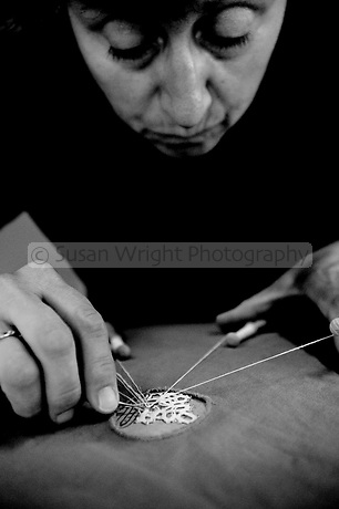 In the school of the Merletto a Tombolo, in Anghiari, women learn the art of bobbin lace or pillow lace.  Here a women is weaving 100% linen thread using wooden bobbins known as 'fuselli or piombini' and held by pins onto a paper design.