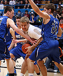 SIOUX FALLS, SD - MARCH 21:  Jordan Unterbrunner #50 from Madison is fouled while trying to go between Isaac Kortemeyer #50 and Jacob Henderson #24 from St. Thomas More in the first half of their Class A Boys semifinal game Friday evening at the Sioux Falls Arena. (Photo by Dave Eggen/Inertia)