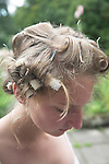 Model released portrait of young teenage girl with curlers in her hair looking down thoughtfully, UK
